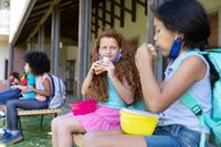 Two girls eating lunch from tiffin box while sitting on bench in the park at school