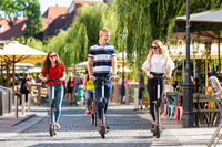 Trendy fashinable group of friends riding public rental electric scooters in urban city environment. New eco-friendly modern public city transport in Ljubljana, Slovenia