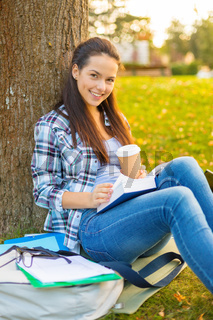 teenager reading book with take away coffee