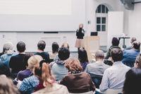 Female speaker giving presentation on business conference.