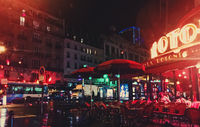 Historical buildings, restaurants and boutique stores on streets of Paris, France at night