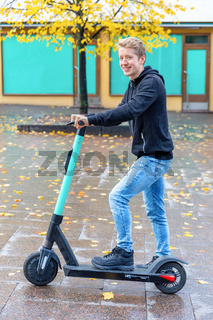 Young man with electric step on the street