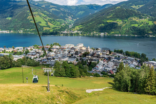 Cityscape of apine city Zell am See and  Zeller Lake in Austria. Summer meadows, ski gondolas, and view of Tirol mountains Alps.