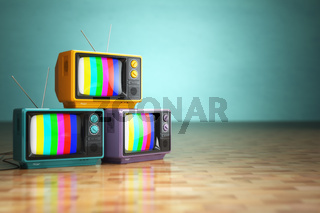 Vintage television concept. Stack of retro tv set on green background.
