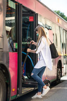 Teenage girl commuter entering city bus carring foldable electric urban scooter, wearing protective face mask against spreading of coronavirus and disease transmission at time of covid-19 pandemic