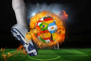 Football player kicking flaming international flag ball