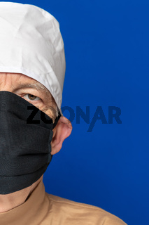 Half face senior adult doctor dressed black surgical face mask, white medical cap, standing against blue background. Close-up head shot