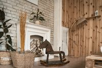 Wooden rocking horse stands in a room by the fireplace. Nearby wicker baskets with plants. High quality photo
