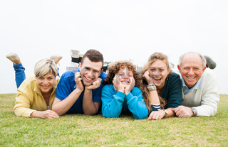Happy family lying on green lawn