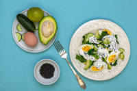 Green salad of spinach, avocado, cucumber and egg.