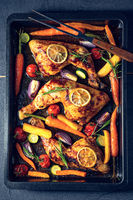 Grilled chicken legs with various vegetables and herbs.