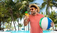 happy man in straw hat with juice on beach