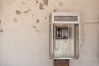 Vintage pay public use phone cabin on white ragged wall