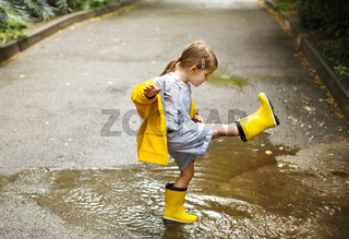 Little girl wearing yellow boots and coat in rainy day