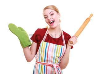 Happy housewife or baker chef wearing kitchen apron green oven mitten holds baking rolling pin studio picture isolated on white