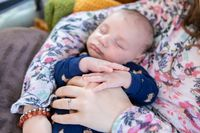 Resting infant cradled in Mother's arms