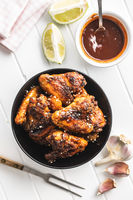 Grilled chicken wings in bowl with BBQ sauce.