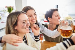 Frauen umarmen sich beim Fußball schauen und stoßen mit Bier an