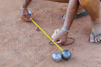 Man measures distance between balls during petanque game