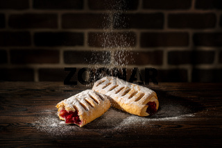 Strudel with cherries powdered with sugar