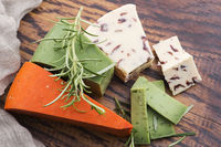 Different types of cheese are cut on a plate with rosemary