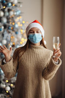 Beautiful young woman in protective mask with glass of champagne