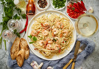 Spaghetti with shrimps on white ceramic plate and served with glass of white wine