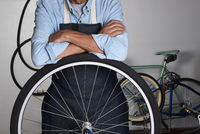 A bicycle repairman standing behind the wheel of a bike in his shop. Man is unrecognizable with his arms folded.