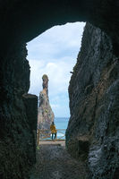 Girl looking at Ribeira da Janela islet between a cave in Madeira