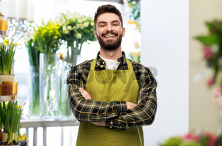 happy young male seller in apron at flower shop