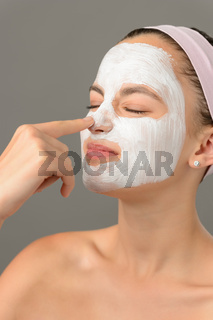 Teenage beauty girl touch nose facial mask