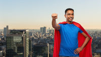 indian man in superhero cape makes winning gesture