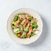 Caesar salad. Grilled chicken breast slices, green romaine salad leaves, croutons and Parmesan cheese, the classic recipe on a white marble background, overhead square shot