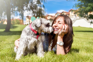 Pretty adult caucasian happy woman resting in the park on a sunny day with her beloved dog. Female lies on the grass, smiling and looking at the camera. love animals concept