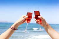 Hands of couple enjoying glasses of champagne on tropical beach