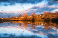 Small pond with reed and moving clouds in the sky