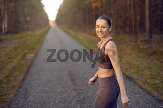 Fit athletic young woman out jogging at sunrise
