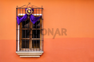 Traditional window on orange wall with semana santa ribbon decoration in Antigua, Guatemala