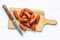Mini salami sausages on wooden cutting board.