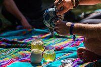 Man pours green tea on picnic blanket