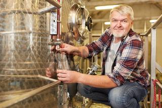 Winzer kontrolliert frischen Wein am Gärtank