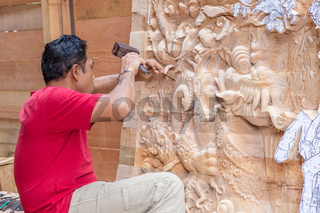 Craftsman carfing a wooden artwork