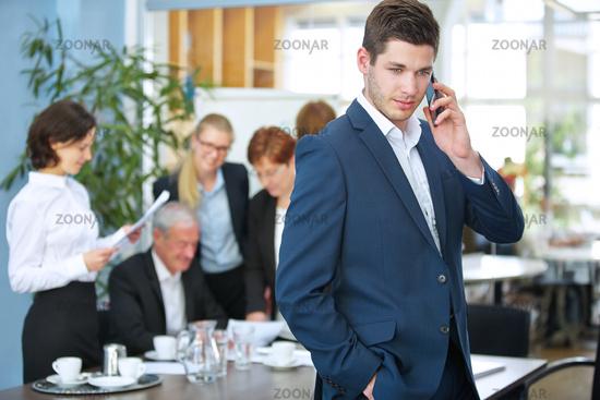 Mann mit Handy telefoniert im Meeting
