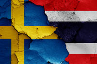 flags of Sweden and Thailand painted on cracked wall