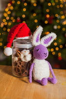 The knitted rabbit next to decorative jar with Christmas hat from above