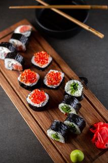 Set of sushi rolls on a black background.
