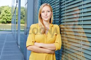 Zufriedene junge Geschäftsfrau vor Büro