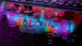 Regentropfen und Pfütze mit reflektierenden Lichtern