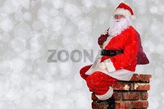 Santa Claus with his bag of toys sitting atop a chminey, with silver bokeh background and snow flake effect.