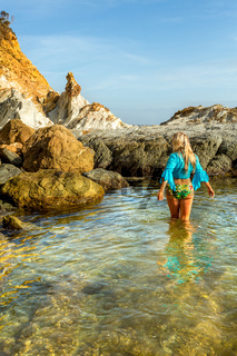 Woman wading into natural rock pool in early morning light